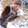 Cute girl playing with snow in a winter park outdoors — Stock fotografie