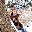 Cute girl hold on to a tree in a winter park outdoors — Stockfoto