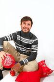 Ung man sitter med jul kuddar isolerad på vita backg — Stockfoto