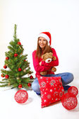 Smiling little girl sitting near a Christmas tree with a teddy b — ストック写真