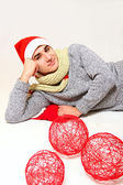 Young man in a Santa Claus hat with red balls isolated on white — Stock Photo