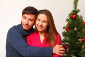 Young man and woman near the Christmas tree isolated — Stock Photo