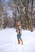 Smiling girl running through the snow in a winter park outdoors — Stock Photo