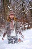 Smiling girl playing with snow outdoors — Stock Photo
