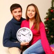 Young man and woman with a clock and a Christmas tree isolated — Stock Photo #15968285
