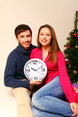 Young man and woman with a clock and a Christmas tree isolated — Zdjęcie stockowe