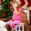 Cute little girl sitting near New Year or Christmas tree and eat - Stock Photo