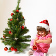 Sweet baby in a hat of Santa Claus sitting near New Year or Chri — Stock Photo
