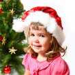 Sweet child near Christmas or New Year tree isolated on white ba — Stock Photo