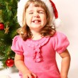 Stock Photo: Laughing baby sitting near New Year or Christmas tree isolated o