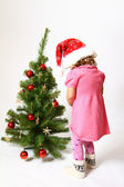 Little girl near New Year tree isolated on white background — Stock Photo