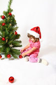 Little girl sitting near New Year or Christmas tree isolated on — Stock Photo