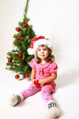 Baby with a hat of Santa Claus, a red ball and a Christmas tree — Stock Photo