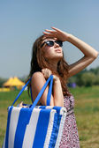 Happy young woman with beach bag — Stock Photo
