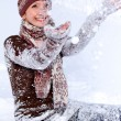Laughing young woman playing with snow outdoors — Stock Photo