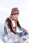 Laughing young woman on the snow outdoors — Stock Photo