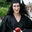 Stock Photo: Caucasian student girl in gown with apple