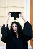 Młody student w sukni, w pobliżu Uniwersytetu, próbuje na pokrywie — Zdjęcie stockowe