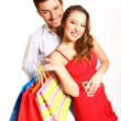 Stock Photo: Young couple with shopping bags hugging isolated on whitebackg