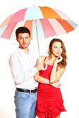 Romantic young couple with a colorful umbrella isolated on white — Stock Photo