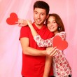 Stockfoto: Happy couple with paper hearts on a background of pink tulle