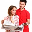 Smiling young couple with a newspaper isolated on white backgrou — Stock Photo #19657185
