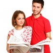 Young couple hugging and reading newspaper isolated on white bac — Stock Photo #19657189