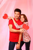 Happy couple with paper hearts on a background of pink tulle — Stock Photo