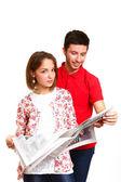 Młoda para czytając gazetę na białym tle — Zdjęcie stockowe