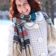Portrait of smiling young woman in a winter park outdoors - Stock Photo