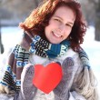 Sweet winter romantic girl holding a red heart outdoors - Stock Photo