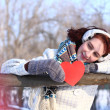 Dreaming winter girl holding red heart outdoors - Foto Stock