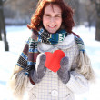 Smiling girl holding a red heart on the background of a winter p — Stock Photo