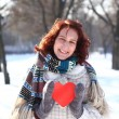 Romantic girl with a red heart on the background of a winter par - Stock Photo