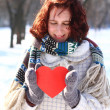 Winter romantic girl holding a heart outdoors - Stock Photo