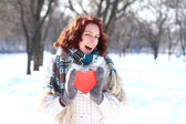 Portrait of winter girl with the red heart outdoors — Stock Photo