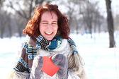 Skrattande flicka med rött hjärta i vinterparken — Stockfoto
