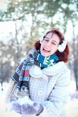 Laughing winter girl holding a snow in hands outdoors — Stock Photo