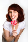 Smiling young woman with lollipop isolated on white background — Stock Photo