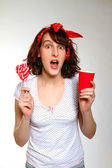 Surprised girl with a lollipop and a cup isolated on a gray back — Stock Photo