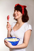 Portrait of happy girl with lollipop and popcorn watching — Stock Photo