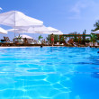 Tourist resort with pool, white parasols and — Stock Photo