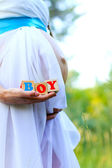 Close-up of the belly of a pregnant woman holding boy cubes out — Stock Photo