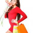 Stock Photo: Happy young girl with shopping bags and bouquet of gerbers on