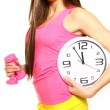 Athletic young woman with a clock and dumbbells — Stock Photo #23385608