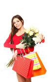 Glad ung kvinna med kassar och en bukett rosor på en — Stockfoto