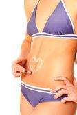 彼女のおなかに日焼け止めクリームから作られた心臓形状を持つ女性 — ストック写真