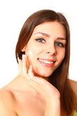 Portrait of an attractive young woman applying cream to her face — Stock Photo