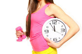 Athletic young woman with a clock and dumbbells — Stock Photo