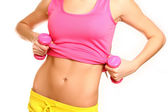 Belly of slim woman with dumbbells on a white background — Stock Photo